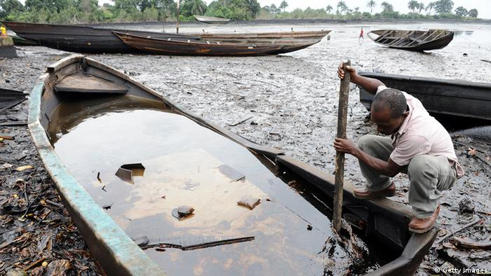 A man tries to separate oil from water inside a canoe in Niger Delta.