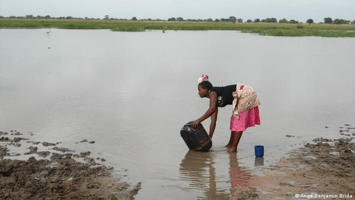 A woman collects water from a flooded area in Mozambique. (Ange-Benjamin Brida)