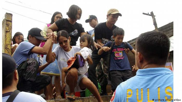 People being helped down a truck. Many regions in the Philippines were evacuated. (Photo. picture alliance November 7, 2013)