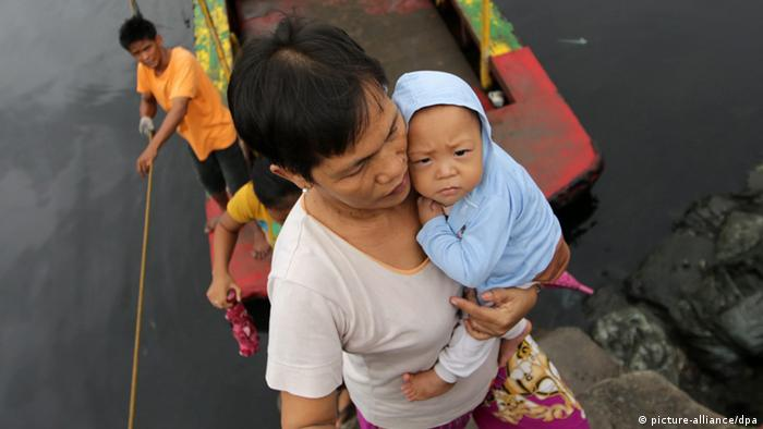 A Filipino resident carries a baby as they cross a river at a coastal village in Las Pinas city, south of Manila