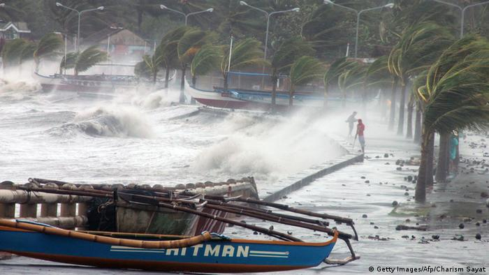 Residents (R) stand along a sea wall as high waves pounded them amidst strong winds as Typhoon Haiyan hit the city of Legaspi, Albay province, south of Manila on November 8, 2013. One of the most intense typhoons on record whipped the Philippines on November 8, killing three people and terrifying millions as monster winds tore roofs off buildings and giant waves washed away flimsy homes. (Photo: AFP)