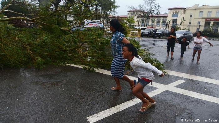 Residents rush to safety past a fallen tree during strong winds brought by Typhoon Haiyan that hit Cebu city, central Philippines November 8, 2013. (Photo: Reuters)