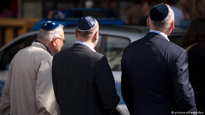 Three men wearing a Jewish skull cap or kippa