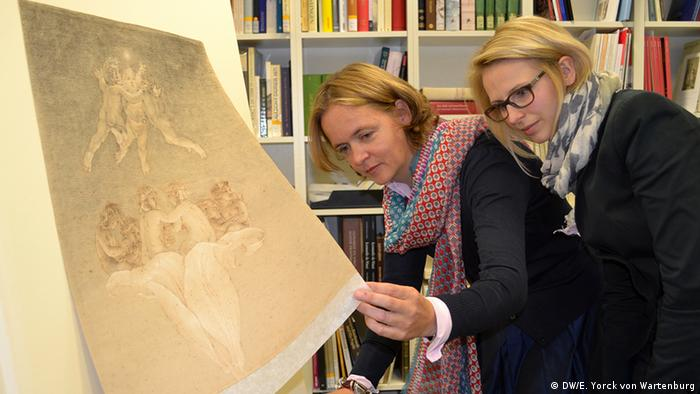 An artwork is in focus at the front, left of the photo as researchers Britta Olényi (left) and Jasmin Hartmann investigate the piece Photo: DW/Elisabeth Yorck von Wartenburg
