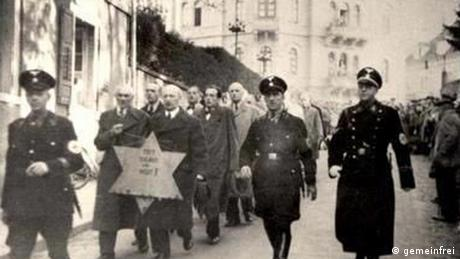 Jews wearing the star of David and Nazi officers march in the streets