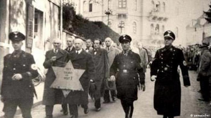 Ne zna se gde je ova fotografiaj snimljena 10.11.1038., ali se vidi da su Jevreji vođeni nacistima, išli ulicama ovog grada, tako da su svi mogli da vide šta se događa.
