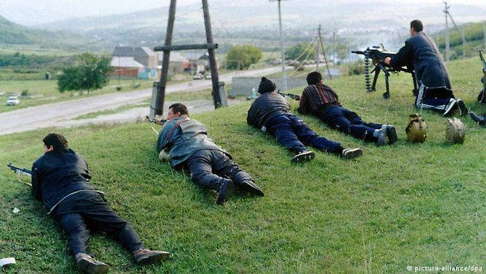 Armed men lie on the ground as a colleague opens fire.