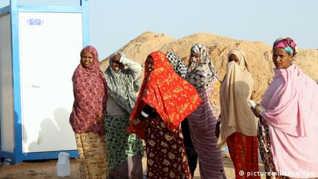 Somali women wearing colorful scarves queue outside a mobile toilet