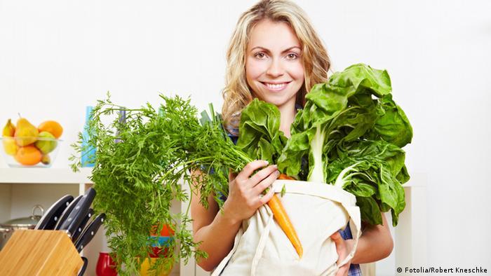 Mulher com sacola de vegetais