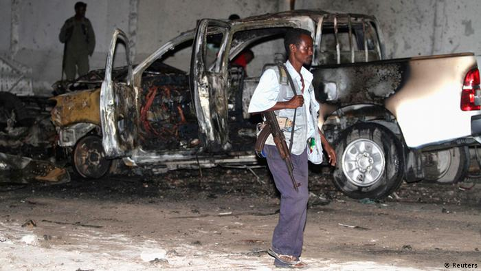 A Somali policeman walks past a burnt car after an explosion outside the Maka Al-Mukarama hotel in Somalia's capital Mogadishu, November 8, 2013. A suspected car bomb attack outside a popular hotel in the Somali capital on Friday evening killed at least six people and left the area covered with blood and burning vehicles, a senior police officer said. REUTERS/Feisal Omar (SOMALIA - Tags: CIVIL UNREST CRIME LAW)