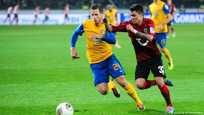 Braunschweig and Hanover players battle for the ball