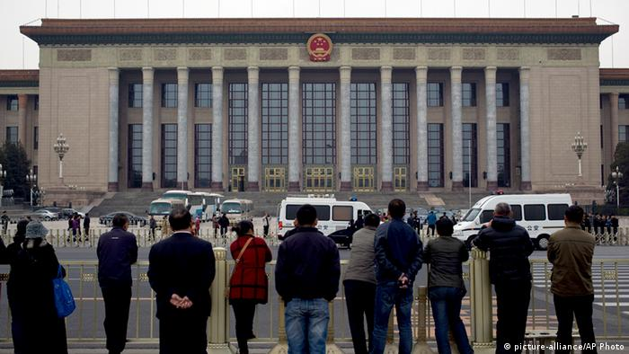 People watch as police officers check visitors in front of the Great Hall of the People during a gathering of the 205-member Central Committee's third annual plenum in Beijing, China Saturday, Nov. 9, 2013. Reform advocates are looking to China's leaders to launch a new era of change by giving entrepreneurs a bigger role in the state-dominated economy and farmers more control over land at a policymaking conference that opened Saturday. (AP Photo/Andy Wong)