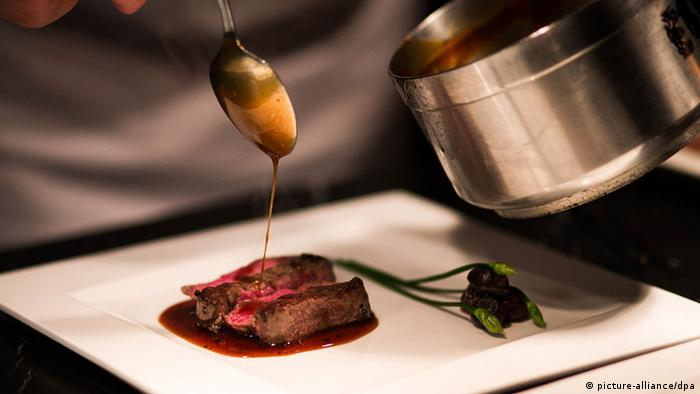 Sauce being drizzled on a gourmet meat dish, Photo: picture-alliance/dpa