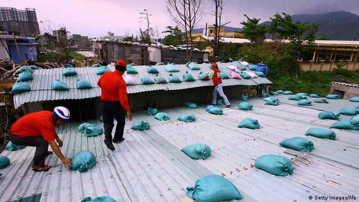 Local Red Cross staff place sand bags on the roof of a house as they prepare for the arrival of super typhoon Haiyan, at a quarter in the central provincial coastal city of Danang on November 9, 2013. Vietnam has started evacuating over 100,000 people from the path of Super Typhoon Haiyan, state media said on November 9, 2013, after the storm tore across the Philippines leaving scores dead and devastating communities. AFP PHOTO (Photo credit should read STR/AFP/Getty Images)