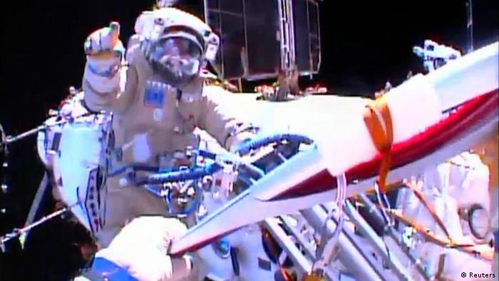 Russian astronaut Oleg Kotov holds an Olympic torch as he takes it on a spacewalk as Russian astronaut Sergei Ryazansky gives instructions outside the International Space Station in this still image taken from video courtesy of NASA TV, November 9, 2013. A pair of Russian cosmonauts took an Olympic torch into open space for the first time in history on Saturday as part of the torch relay of the Sochi 2014 Winter Games. REUTERS/NASA TV/Handout via Reuters