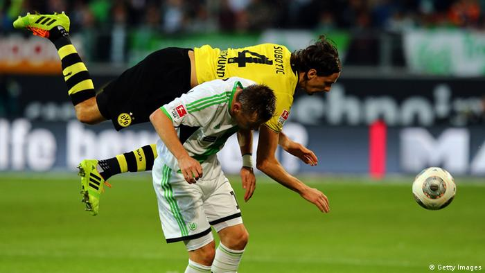 Ivica Olic of Wolfsburg and Neven Subotic of Dortmund battle for the ball