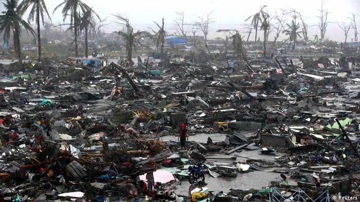 Survivors stand among debris and ruins of houses destroyed after Super Typhoon Haiyan battered Tacloban city in central Philippines November 10, 2013. (Photo: REUTERS/Erik De Castro)