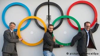ARCHIV - Der erste Bürgermeister von Garmisch-Partenkirchen, Thomas Schmid (l-r), der Skisprung-Olympiasieger Sven Hannawald und der SPD-Fraktionsvorsitzende Markus Rinderspacher (SPD) stehen am 07.11.2013 vor den Olympischen-Ringen, die unter dem Schanzentisch der Skisprungschanze in Garmisch-Patenkirchen (Bayern) befestigt sind. Am 10.11.2013 finden in München, Garmisch-Partenkirchen und den Landkreisen Traunstein und Berchtesgaden Bürgerentscheide um die Einreichung der Bewerbung für die Olympischen Winterspiele 2022 statt. (Foto: Peter Kneffel/dpa)