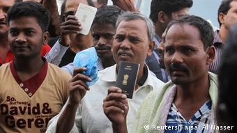 Foreign workers hold their passports as they gather outside a labour office, after missing a deadline to correct their visa status, in Riyadh November 4, 2013. The streets of the Saudi capital Riyadh were unusually quiet on Monday as many expatriates stayed at home to avoid the start of a government crackdown on illegal foreign workers. REUTERS/Faisal Al Nasser (SAUDI ARABIA - Tags: POLITICS BUSINESS EMPLOYMENT SOCIETY IMMIGRATION)