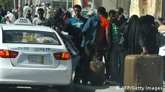 Foreign workers wait for a taxi as they leave Manfuha (Photo: FAYEZ NURELDINE/AFP/Getty Images)