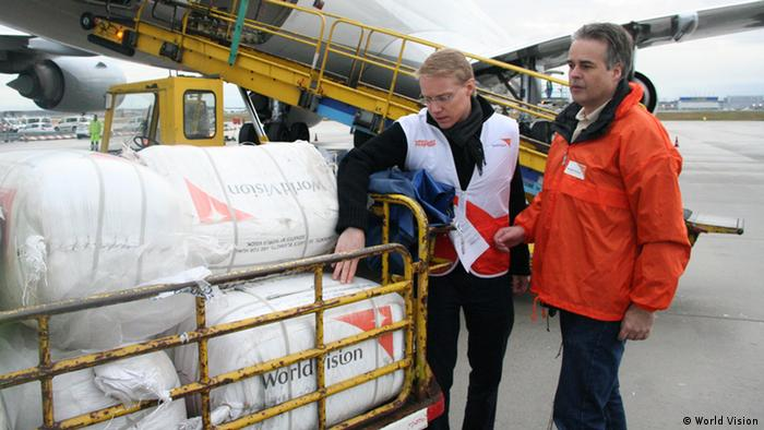 Two relief workers looking at aid supplies to be sent to the Philippines