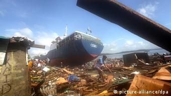 A Filipino woman walks by a ship washed ashore in the super typhoon devastated city of Tacloban, Leyte province, Philippines, 10 November 2013. (Photo: dpa)