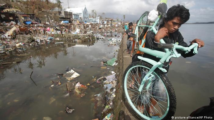 A resident carries his bicycle past houses damaged by typhoon Haiyan, in Tacloban city, Leyte province central Philippines