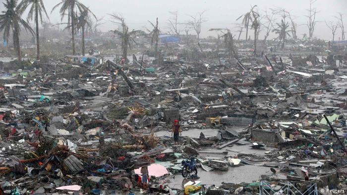 Survivors stand among debris and ruins of houses destroyed after Super Typhoon Haiyan battered Tacloban city in central Philippines November 10, 2013