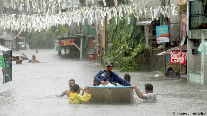 Filipino residents wade in chest deep flood waters caused by typhoon Fengshen in San Juan, east of Manila