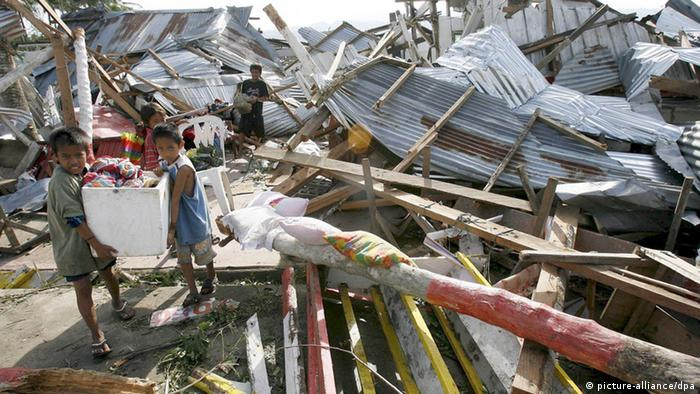 Filipino children carry their belongings after their house was damaged by typhoon Durian in Albay province