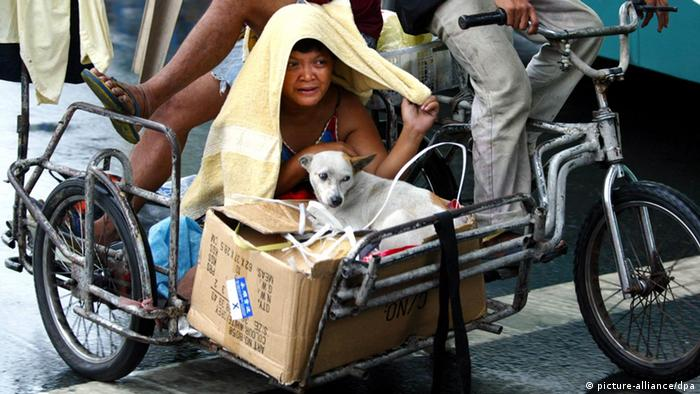 A Filipino woman aboard a passenger bike uses a towel to protect herself from the rain in Manila