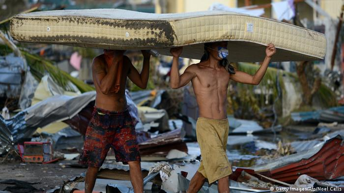 Residents carry a mattres taken from a hotel in Palo, eastern island of Leyte on November 10, 2013, three days after devastating Super Typhoon Haiyan hit the area on November 8. The death toll from a super typhoon that decimated entire towns in the Philippines could soar well over 10,000, authorities warned on November 10, making it the country's worst recorded natural disaster. AFP PHOTO / NOEL CELIS (Photo credit should read NOEL CELIS/AFP/Getty Images)
