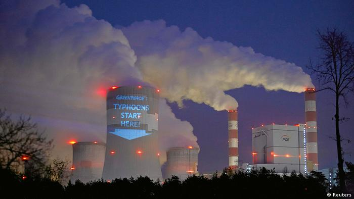 A slogan is projected by Greenpeace on a cooling tower of Belchatow Power Station, Europe's largest coal-fired power plant, in central Poland