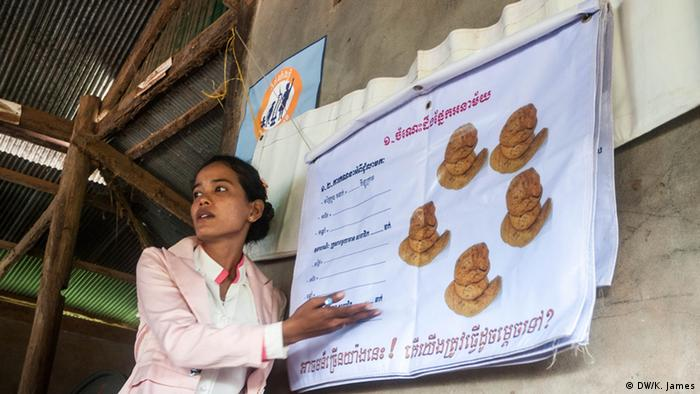 A cambodian women stands next to a poster with pictures of feces, giving a presentation to villagers about health and sanitation (photo: Kyle James)