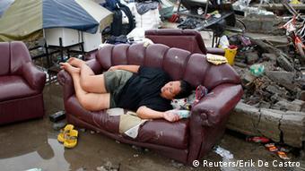 Ein erschöpftes Opfer des Taifuns ruht auf einem Sofa unter freiem Himmel (Foto: REUTERS/Erik De Castro)