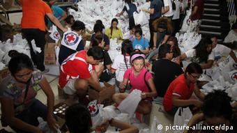 epa03946220 A handout picture made available by the Philippine Red Cross (PRC), shows volunteers helping in packing relief goods for typhoon-affected families in Manila, Philippines, 12 November 2013. International aid poured in for the Philippines as authorities stepped up efforts to reach survivors driven to looting after one of the world's strongest typhoons devastated their towns. A tropical depression brought heavy rains over the central and eastern Philippines, where provinces badly hit by Haiyan are located, raising concerns that relief operations would be hampered. EPA/PHILIPPINE RED CROSS HANDOUT EDITORIAL USE ONLY/NO SALES