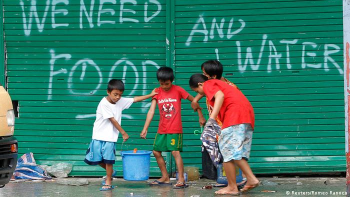 Children help to carry pails of drinking water as they walk past a graffiti calling for help after Typhoon Haiyan devastated Tacloban city, central Philippines November 12, 2013. Rescue workers tried to reach towns and villages in the central Philippines on Tuesday that were cut off by the powerful typhoon, fearing the estimated death toll of 10,000 could jump sharply, as relief efforts intensified with the help of U.S. military. REUTERS/Romeo Ranoco (PHILIPPINES - Tags: DISASTER ENVIRONMENT)
