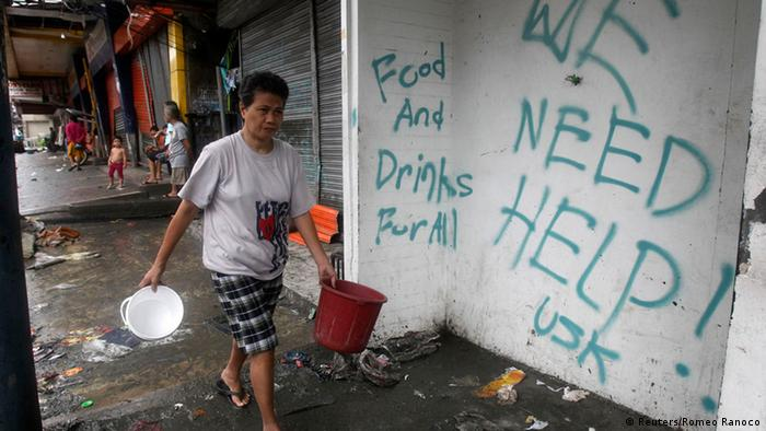 A resident walks past a wall with a graffiti calling for help after Typhoon Haiyan devastated Tacloban city, central Philippines November 12, 2013. Rescue workers tried to reach towns and villages in the central Philippines on Tuesday that were cut off by the powerful typhoon, fearing the estimated death toll of 10,000 could jump sharply, as relief efforts intensified with the help of U.S. military. REUTERS/Romeo Ranoco (PHILIPPINES - Tags: DISASTER ENVIRONMENT)