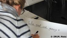 """Ein Mädchen schreibt auf ein Plakat """"Wie viel ist genug?"""". Foto: Madelaine Meier (DW), 9.11.2013, Dortmund"""