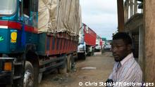 A man watches as a convoy of lorries drives past on the border between Ghana and Ivory Coast (Chris Stein/AFP/GettyImages)