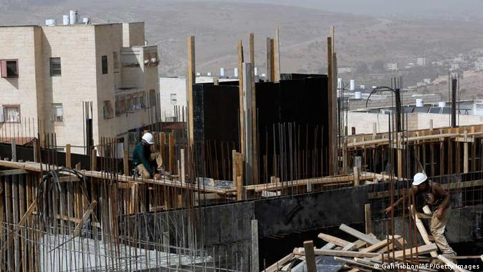 Palestinian laborers work on a construction site in Ramat Shlomo, a Jewish settlement in the mainly Palestinian eastern sector of Jerusalem, on October 30, 2013. (photo via Getty Images)