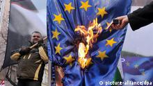 epa03059516 The hand of Elod Novak (R), one of the Vice-presidents of the radical nationalist party Jobbik, is seen pointing at a burning European flag which is held by co-Vice-president Csaba Gyuere (L) during their party's demonstration titled 'Members or be free' in front of the building of the European Commission Representation in Budapest, Hungary, 14 January 2012. EPA/SZILARD KOSZTICSAK HUNGARY OUT