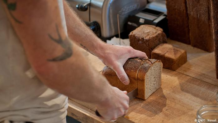 Josey Baker slicing bread at The Mill in San Francisco, Copyright: DW/Candice Novak November 2013 in San Francisco