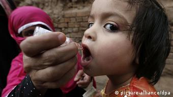 A polio worker administers polio vaccine to a child, in Peshawar, the provincial capital of Khyber-Pakhtunkhwa province, Pakistan, 24 October 2013 (Photo: EPA/ARSHAD ARBAB)