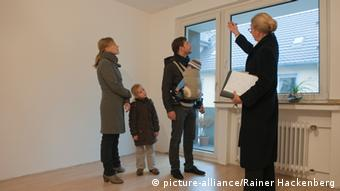 family and real estate agent looking at room