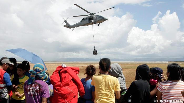Ein US-amerikanischer Blackhawk Hubschrauber bringt Wasser und Lebensmittel ins Katastrophengebiet (Foto: EPA/RITCHIE TONGO)