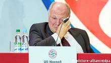 Präsident des FC Bayern München Uli Hoeneß reibt sich am 13.11.2013 in München (Bayern) während der Jahreshauptversammlung des Fußball-Bundesligisten FC Bayern München auf dem Podium mit einem Taschentuch die Augen. Foto: Marc Müller/dpa