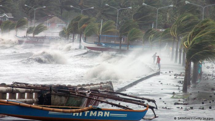 GettyImages 187331509 Residents (R) stand along a sea wall as high waves pounded them amidst strong winds as Typhoon Haiyan hit the city of Legaspi, Albay province, south of Manila on November 8, 2013. One of the most intense typhoons on record whipped the Philippines on November 8, killing three people and terrifying millions as monster winds tore roofs off buildings and giant waves washed away flimsy homes.AFP PHOTO/CHARISM SAYAT (Photo credit should read Charism SAYAT/AFP/Getty Images)