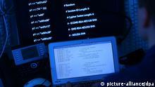 ILLUSTRATION - Ein Mann sitzt am 25.04.2013 in Köln (Nordrhein-Westfalen) vor einem Rechner mit Computer Quellcode auf dem Bildschirm. Weltweit haben Angriffe von Computer Hackern und die Cyber Kriminalität insgesamt zugenommen. Foto: Oliver Berg/dpa