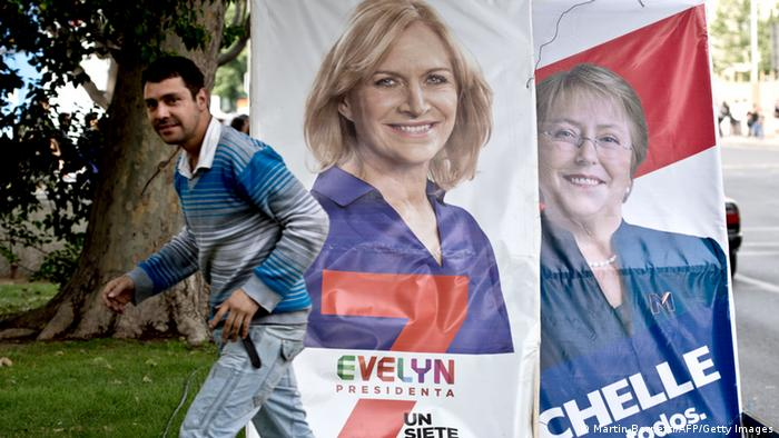 A passer-by walks next to electoral propaganda posters of Chilean presidential candidate Michelle Bachelet (R), of the New Majority Coalition, and Evelyn Matthei, of theright-wing Democratic Independent Union party in Santiago, on October 29, 2013. According to last surveys, Chile's former president and socialist candidate Michelle Bachelet, is the favourite to win the November 17 presidential election. AFP PHOTO/MARTIN BERNETTI (Photo credit should read MARTIN BERNETTI/AFP/Getty Images)